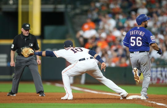 Sep 17, 2019; Houston, TX, USA; Texas Rangers catcher Jose Trevino (56) beats the throw to Houston Astros first baseman Yuli Gurriel (10) in the fifth inning at Minute Maid Park. The call was reviewed and Trevino was called out. Mandatory Credit: Thomas B. Shea-USA TODAY Sports