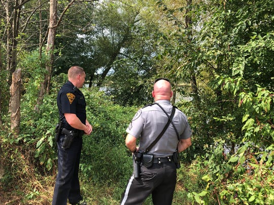 Haddon Township Officer William Moore (left) and Collingswood Officer Kenneth Jacoby survey woods along the Cooper River, near the site where they made a Sept. 1 water rescue.