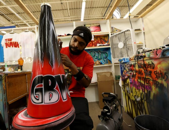 Airbrush artist CJ Fleming, 35, of Pontiac works on the cheerleader bullhorn of a client at his store inside the Dixieland Flea Market in Waterford, Saturday, Aug. 3, 2019.