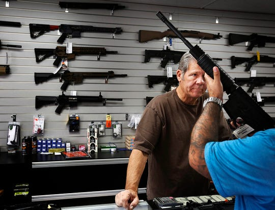 Gunsmith, Frank Cobet, of the Get Loaded gun store in Chino, Calif., shows a customer an AR-15 rifle in this Tuesday, Dec. 8, 2015, file photo. Gunmaker Colt says on Sept. 19, 2019, it is suspending its production of rifles for the civilian market including the popular AR-15.