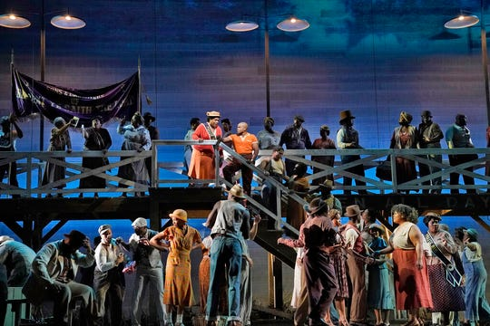 "This image released by the Metropolitan Opera shows Latonia Moore as Serena, center left on stairs, and Frederick Ballentine as Sportin' Life in a scene from the Gershwins' ""Porgy and Bess."""