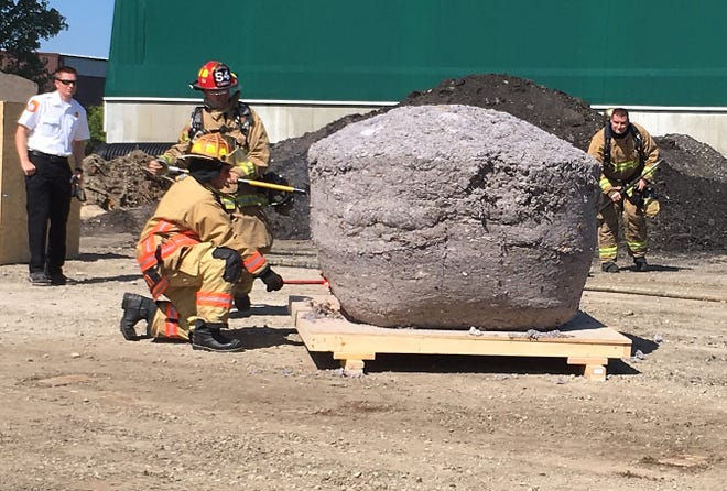 Fire marshall Jason Baloga, left, watches as three of his firefighters try to set the world record lint ball aflame.