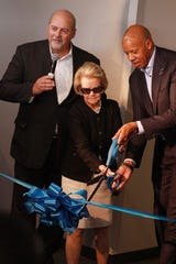Master of ceremonies Bob Riney looks on as Detroit Lions owner Martha Ford and Henry Ford Health System CEO and President Wright Lassiter III cut the ribbon on the new William Clay Ford Center for Athletic Medicine.