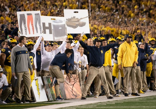 Michigan student managers hold up play cards behind Jim Harbaugh during the season opener against Middle Tennessee.