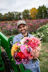 Michael Genovese stands in the fields of his Summer Dreams Farms, a dahlia farm in northern Oakland County. Established in 2015, it's now one of the biggest dahlia farms in the Midwest.