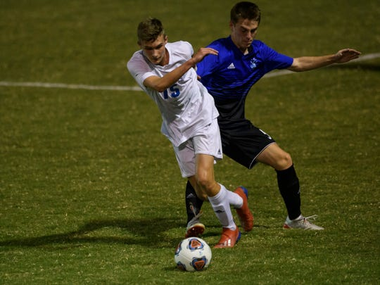 Memorial's Tyler Beeler (15) and Castle's Sean Kelly (5) fight for possession of the ball at Castle Soccer Stadium in Newburgh, Ind., Wednesday night, Sept. 18, 2019. The Tigers defeated the Knights, 1-0.