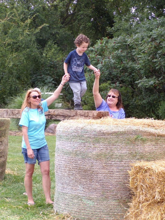 "Christian, 4, walks the ""balance beam"" with assistance from Krista and Sheree Dirschell. This activity was included in the haybale obstacle course."