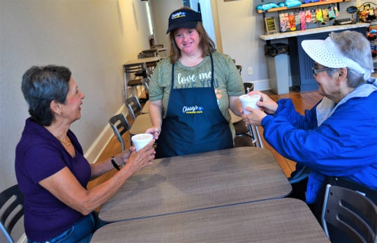 Christy's Corner Café employee Emily Kehlmeier serves customers Delores Henry, left, and Alice Jessee.