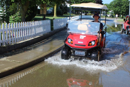 A man drives a golf cart through a flooded street on South Bass Island July 11. Lake Erie's high water levels contributed to widespread coastal flooding this year in communities like Put-in-Bay, Port Clinton and other parts of Ottawa County.