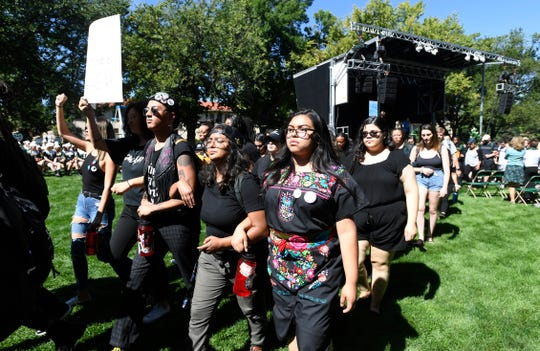 Protesters silently walk between the stage and the crowd as Colorado State University President Joyce McConnell speaks during the annual President's Fall Address on the Colorado State University campus on Thursday, Sept. 19, 2019.
