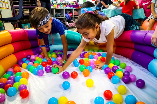 "Vinicius Gonzaga, 6, and classmate Dayna Castro, 6, reach for a ""gum ball"" as they do math in their class. Rock Your School Day at Gulf Elementary in Cape Coral rocked the school. They joined a nationwide effort to promote outside-the-box learning."