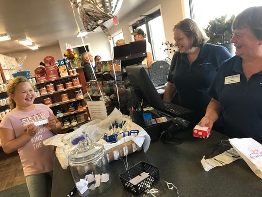 Eight-year-old Krysten Derrig of Kewaunee checks out some of the items at the front counter with sales associates Becky Paplham and Sue Wojta, from left, during the Sept. 18 grand opening for Kewaunee Hometown Pharmacy.