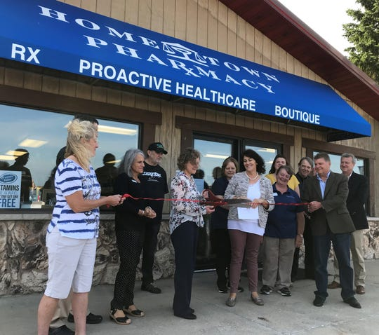 Sarah Bartel, part-owner and partner pharmacist, cuts the ribbon Sept. 18 at a grand opening ceremony for Kewaunee Hometown Pharmacy. To Bartel's right is Mayor Sandi Christman.