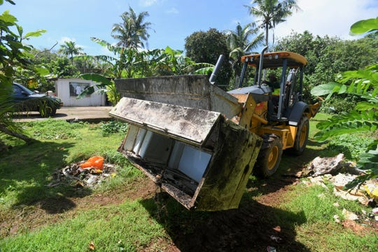 A Department of Public Works employee uses a backhoe to remove an old refrigerator from the property of a family residing on Swamp Road in Dededo on Thursday, Sept. 19, 2019.
