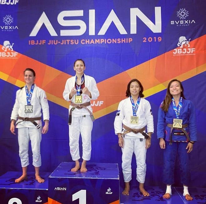Tracy Matanane, at top, celebrates her gold medal in the adult brown belt featherweight division.