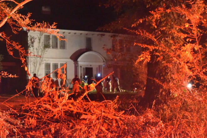 First responders wrap up a 5-hour-long firefight at a Jackson residence on the 1700 block of North Highland Avenue as the red lights from emergency vehicles glare off of nearby vegetation on Wednesday.