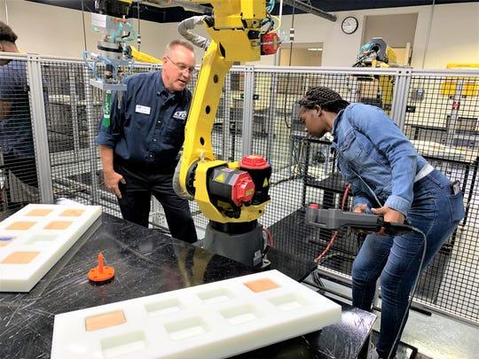 Milwaukee high school student Natori Dixon-McNeil gets a close look at a Fanuc robot as Lakeshore Technical College robotics expert Jim Gruenke guides her through her programming.