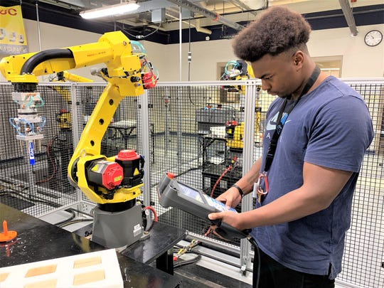 Milwaukee high school student Nathan Mason uses a teach pendant to interface with the Fanuc robot he is learning to program at Lakeshore Technical College.