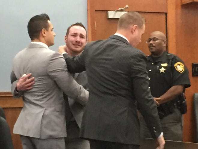A tearful Guy Mitchell celebrates with defense attorneys Justin Weatherly, left,  and Brandon Henderson after a jury found him not guilty of aiding and abetting murder and involuntary manslaughter.