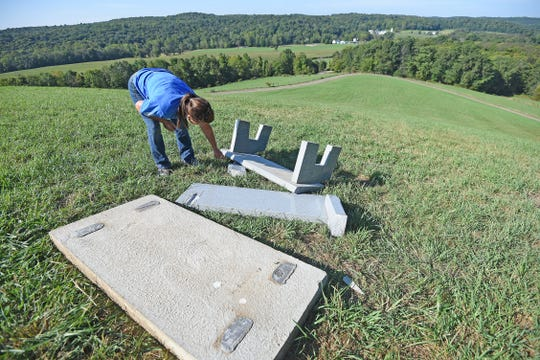 Gail Herron of the Ohio Department of Natural Resources looks closely for damage to the bench memorializing longtime News Journal writer and columnist Ron Simon. The bench was flipped over.