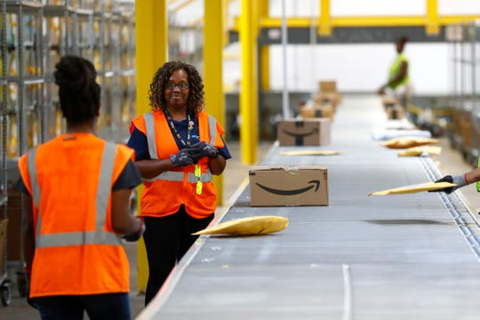Workers stow packages at Amazon's Memphis delivery station facility on Thursday, Sept. 19, 2019.