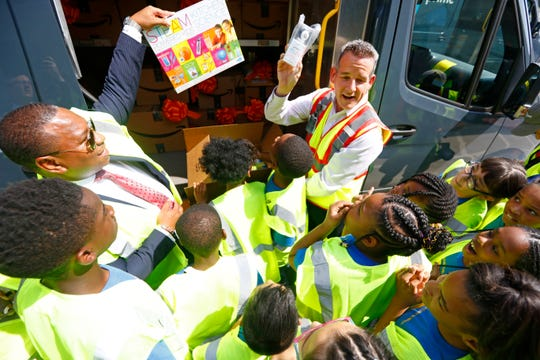 Shelby County School Superintendent Joris Ray helps Amazon Regional Director of Operations James Shivley surprise children from Getwell Elementary School with a donation of $10,000 of STEM supplies during the grand opening of Amazon's Memphis delivery station facility on Thursday, Sept. 19, 2019.