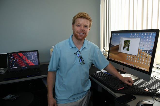 Owner Tyler Parrish works on both PC and Macintosh computers. Marco Island Computers has moved to larger quarters in the Regions Bank building and added staff.