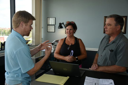 Owner Tyler Parrish, returns a repaired laptop to Kathy and Brad Laubach of Fiddler's Creek.  promotes every-day availability. Marco Island Computers has moved to larger quarters in the Regions Bank building and added staff.