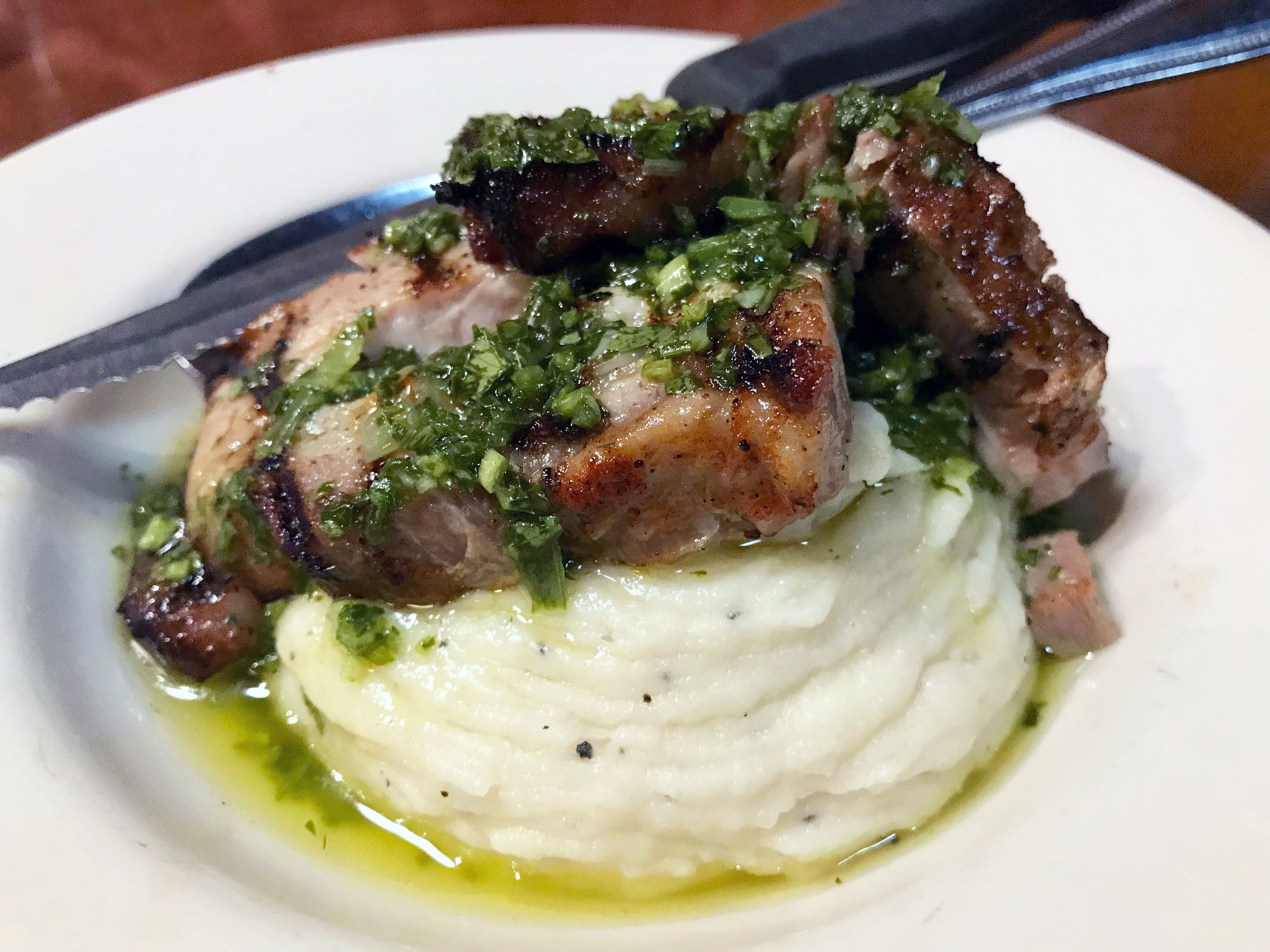 Pork belly from Maple Creek Farm in Waukesha is sauced with chimichurri and draped over garlic mashed potatoes, a special at La Merenda, 125 E. National Ave.