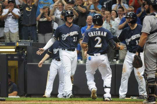 Brewers centerfielder Trent Grisham  is greeted by Travis Shaw (21) and Keston Hiura after both Grisham and Shaw scored as a result of bad throws in the sixth inning.