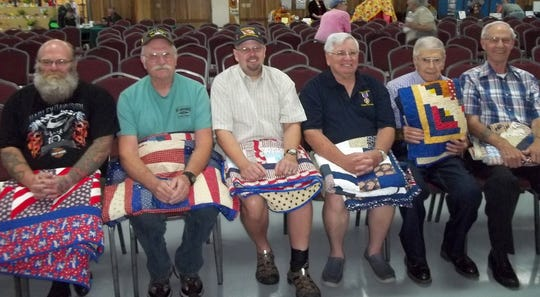 Six Twin Lakes Area veterans were honored as the annual Mountain Home Quilts of Valor at the Baxter County Fair. The Alley-White American Legion Post #52 provided a Color Guard, while Katie Wilson served as  vocalist for the National Anthem and the Pledge of Allegiance. Veterans awarded Quilts of Valor were: (from left) Christopher Buresh, U.S. Army; Roger Buresh, U.S. Army; Eldon Cooper, U.S. Army, Bronze Star; John Templeton, U.S. Marine Corps, Purple Heart, Matthew Yancik, U.S. Army; and Benny Speaks, U.S. Navy. The recipients served in wars from World War II (Yancik), Vietnam, Desert Storm, Iraqi Freedom and Enduring Freedom, with some serving multiple deployments.