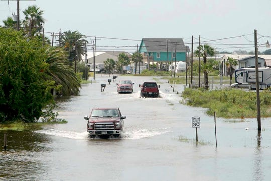 Trucks drive down Carancahua Street to enter neighborhoods in Sargent, Texas, Wednesday, Sept. 18, 2019. Imelda has deluged parts of Southeast Texas with nearly 20 inches of rain, but officials in Houston and surrounding communities said Wednesday that so far there have been no severe impacts from the tropical depression. (Mark Mulligan/Houston Chronicle via AP)
