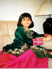 Rupali Patel, around age 7, wearing a traditional choli suit in her family's apartment in Clarksville, shortly after the family moved there from India.