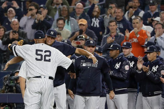 New York Yankees starting pitcher CC Sabathia, left, hugs relief pitcher Dellin Betances while teammates watch as he leaves during the third inning of the team's baseball game against the Los Angeles Angels on Wednesday, Sept. 18, 2019, in New York. (AP Photo/Frank Franklin II)