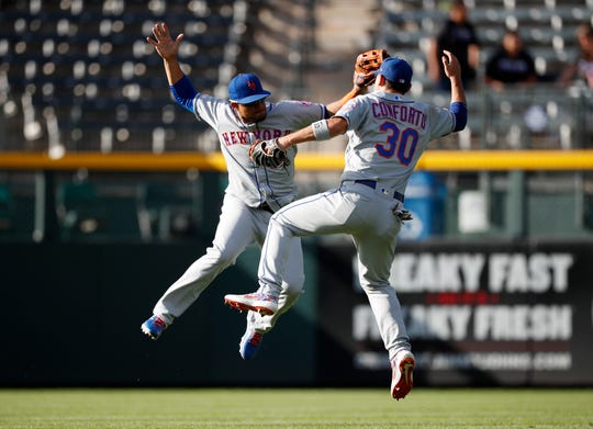 New York Mets center fielder Juan Lagares, left, celebrates with right fielder Michael Conforto after the ninth inning of a baseball game against the Colorado Rockies Wednesday, Sept. 18, 2019, in Denver. The Mets won 7-4.