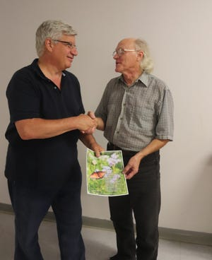 Dale Taylor, right, president of the Doña Ana Photography Club, congratulates Seth Madell, left, editor of the newsletter.