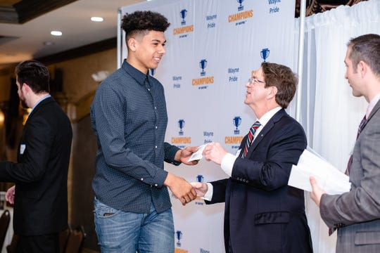 A student receiving a $200 check at a Champions of Wayne banquet.