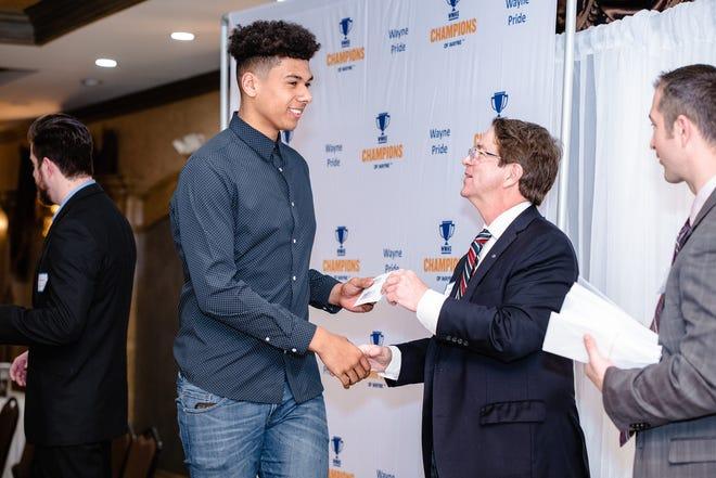 A student receiving a $200 check at a Champions of Wayne banquet.