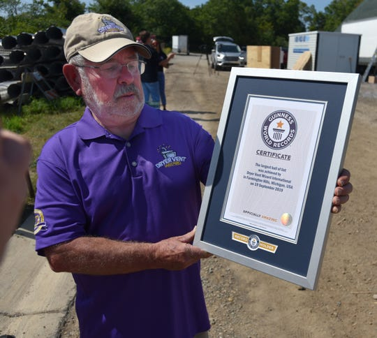 A representative of Dryer Vent Wizard International holds a certification of their Guinness Book of World Records lint pile.