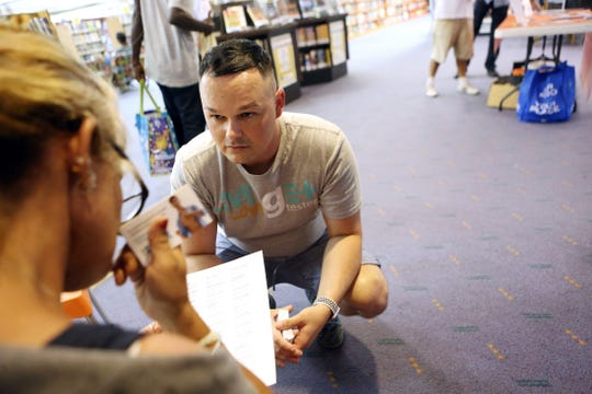 Desert AIDS Project interim director of community health, C.J. Tobe, shares a list of doctors with Amy Horn, 48, inside the Palm Springs Public Library on Tuesday, July 23, 2019. In addition to free HIV and Hepatitis C testing, Desert AIDS Project helps people access insurance programs.