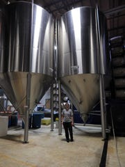 Lead Brewer Kristin Luparello stands in front of two enormous tanks at SanTan's production facility in Chandler.