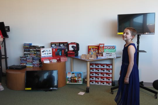 Peyton Gonzales shows the gifts she is donating to the children at Cardon Children's Medical Center.