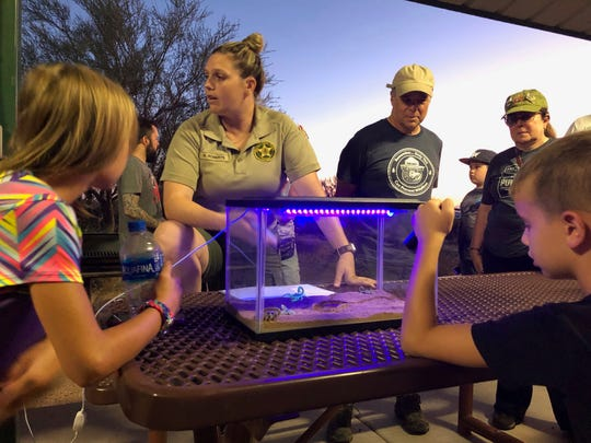 This Aug. 18, 2019 photo shows Park Ranger Anna Roberts, center, talking about scorpions and how to catch them in Lost Dutchman State Park, Ariz. Feared, admired and loathed, scorpions have roamed the earth for 450 million years. An interesting way to learn about the critters, which glow under black lights, is to go on scorpion hunts in Southwest states like Arizona and New Mexico. Wear closed-toed shoes and pants, bring black lights and prepare to be awed.