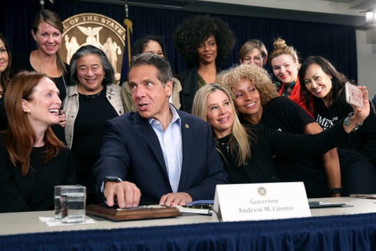 Surrounded by supporters and activists, New York Gov. Andrew Cuomo signs a bill that increases the statute of limitations in rape cases during a bill signing ceremony in New York, Wednesday, Sept. 18, 2019. Actresses Julianne Moore, left, Mira Sorvino, fourth from right, and Michele Hurd, third from right, were there as supporters of the bill and as members of the Time's Up movement, which advocates for women's rights. (AP Photo/Seth Wenig)