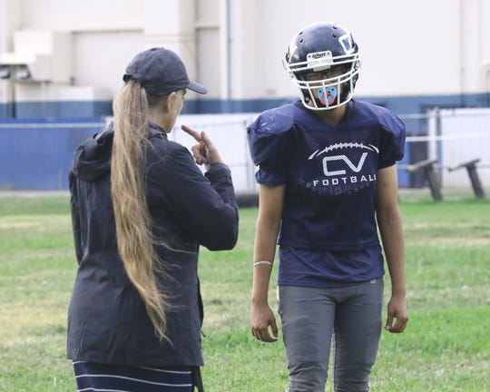 Interpreter Kellie Miller tells Central Valley football player Jairo Muñoz what the coaches are saying during practice on Wednesday, Sept. 18, 2019.