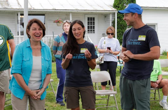 U.S. Sen. Amy Klobuchar, left, laughs with farmers Thelma Heidel-Baker, center, and Ricky Baker, right, during a visit to the Organic Valley Cooperative Dairy Farm named Bossie Cow Farm, Thursday, Sept. 19, 2019, in Random Lake, Wis.