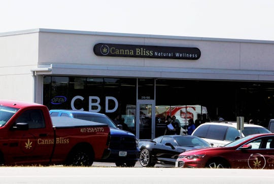 People stand outside of Canna Bliss in Springfield, Mo., during a Health City MD cannabis clinic on Monday, Sept. 16, 2019.