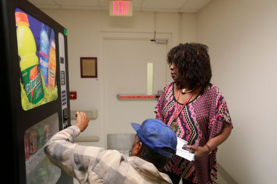 Miracle Hill Nursing and Rehabilitation Center Social Worker Angeles Allen helps a resident get a soda from a vending machine Wednesday, Sept. 18, 2019.