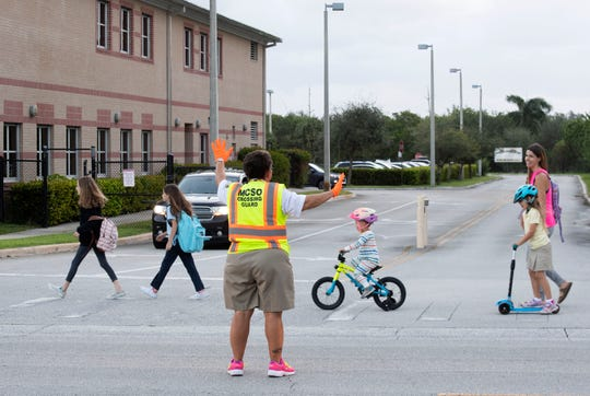 "Michelle Strunk, begins her duties Thursday, Sept. 19, 2019, as one of five Hobe Sound Elementary School crossing guards daily at 6:45 a.m., a role she has flourished in for 28 years. ""I enjoy my kids. I love my kids,"" Strunk said. ""I've had people tell me, 'your smile gets me going for the day.'"""