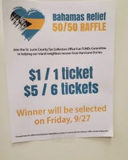 A flyer posted at each of the St. Lucie County Tax Collector's offices announces a raffle to benefit the Bahamas as well as the office's annual holiday party.